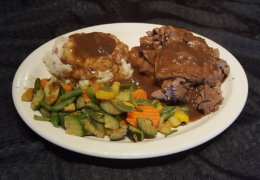 Hot Beef Sandwich piled high on Texas Toast, with veggies, and creamy mashed potatoes topped with beef gravy